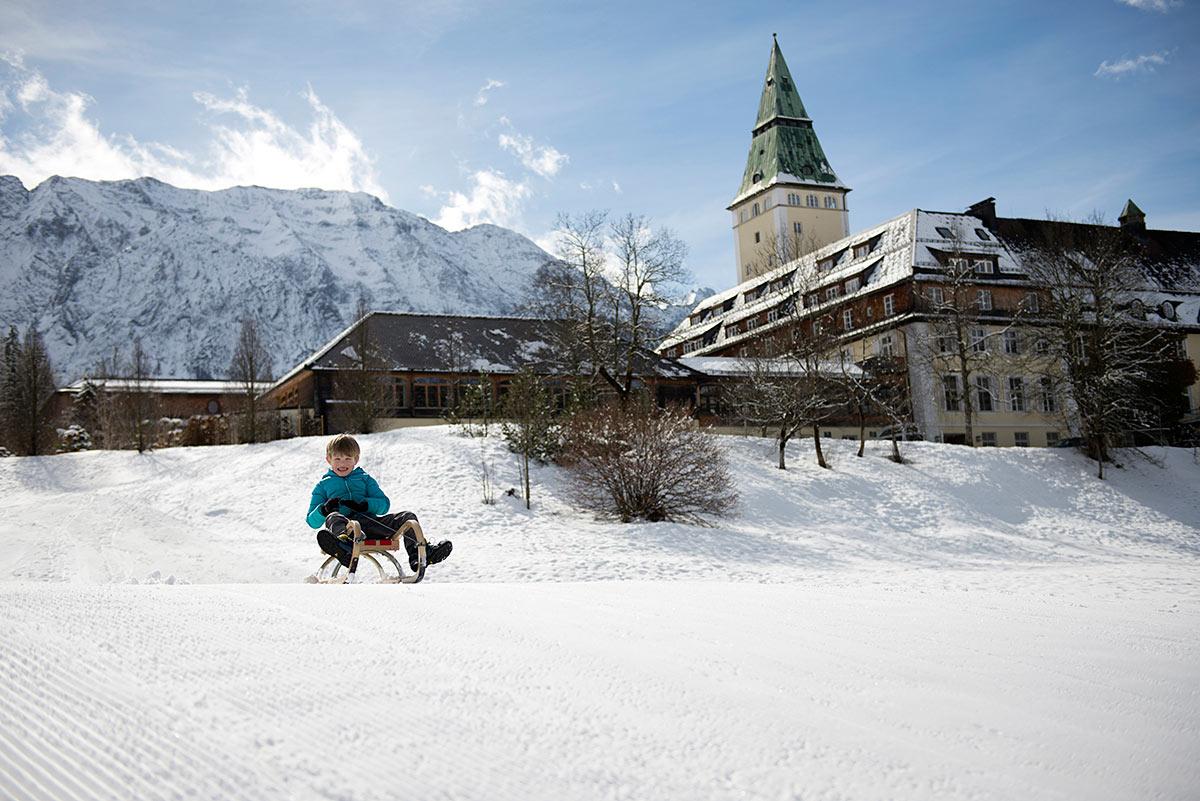 Kind auf Schlitten im Schnee vor Schlosselmau mit Wettersteinwand |Felix Krammer Fotografie