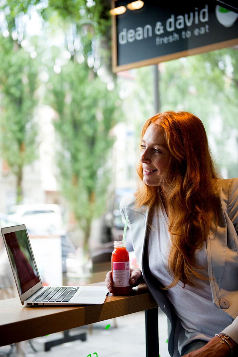 Werbefotografie für Dean & David: junge Frau sitzt mit Notebook am Fenster, in der Hand hält sie ein Getränk. |Felix Krammer Fotografie