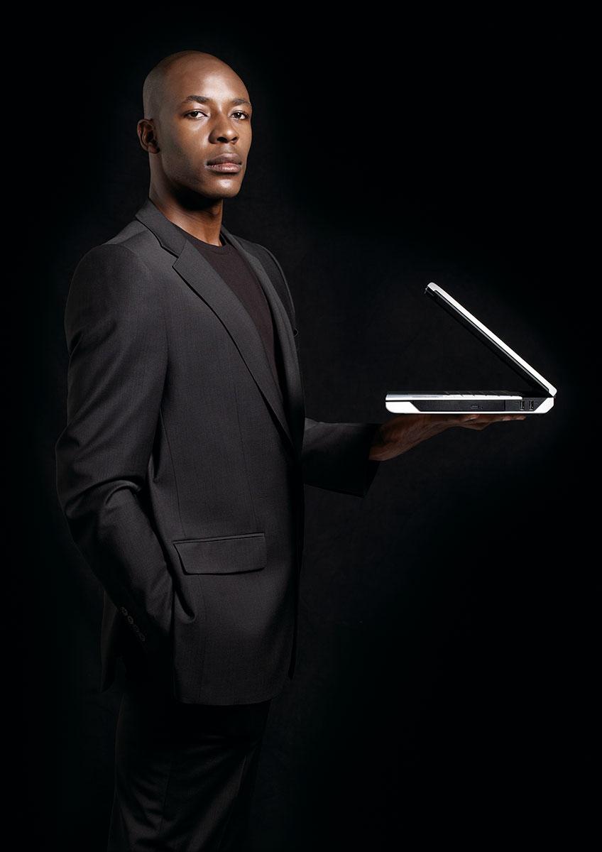 Farbiger Mann stehend mit Notebook – Werbefotografie für Fujitsu Siemens Computers. |Felix Krammer Fotografie