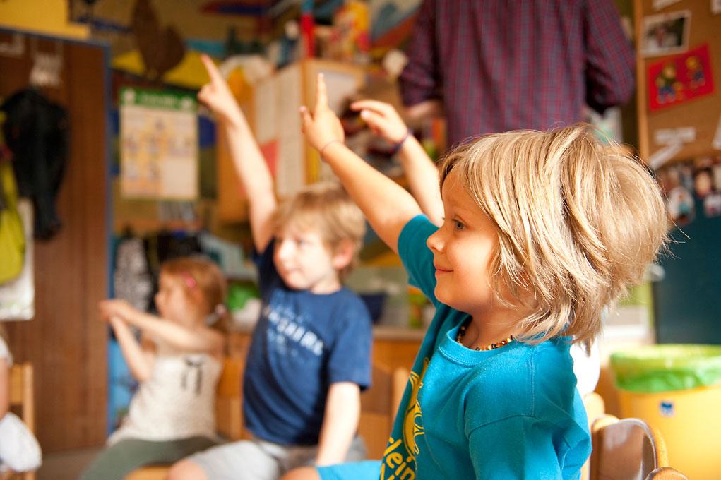 Kindergartenfotografie - Junge im Stuhlkreis meldet sich. |Felix Krammer Fotografie