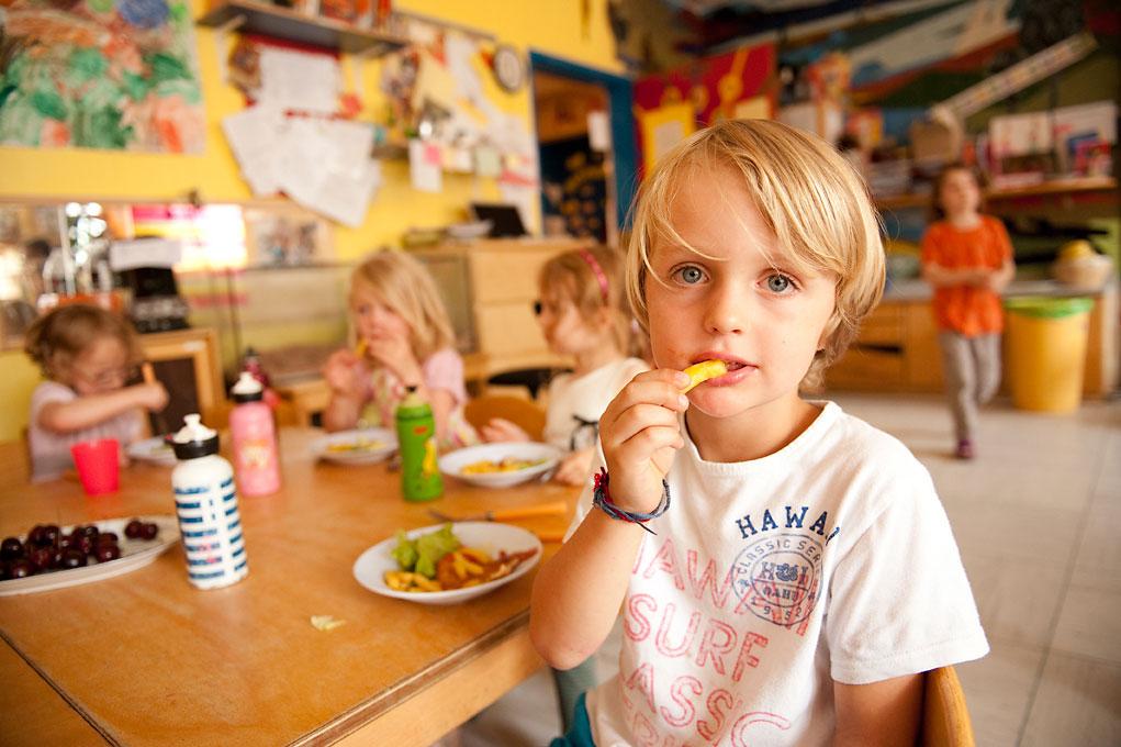 Kinderfotografie eines Jungens im Kindergarten beim Mittagessen mit Pommes in der Hand. |Felix Krammer Fotografie
