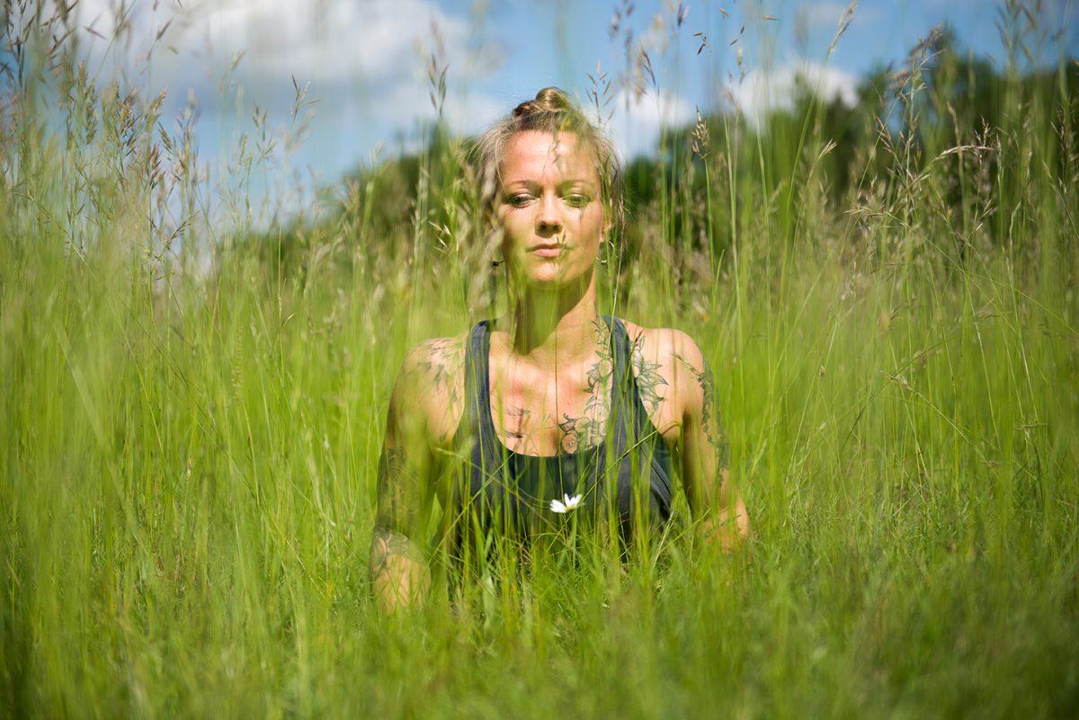 Yogafotografie von Yogalehrerin Stine Matthes in der Yogahaltung Bhujangasana im hohen Gras. |Felix Krammer Fotografie