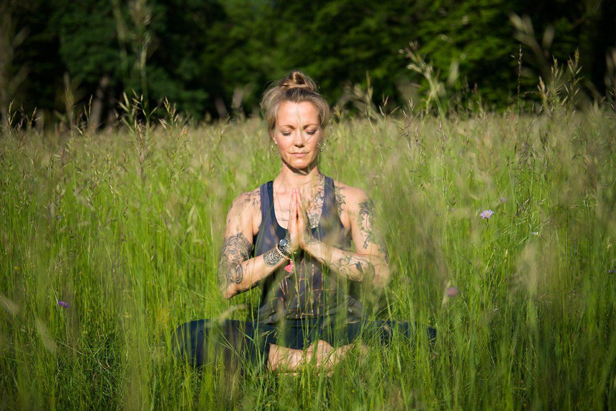 Yogafotografie - Yogalehrerin Stine Matthes sitzt meditierend im Gras, die Hände vor der Brust im Anjali Mudra. |Felix Krammer Fotografie