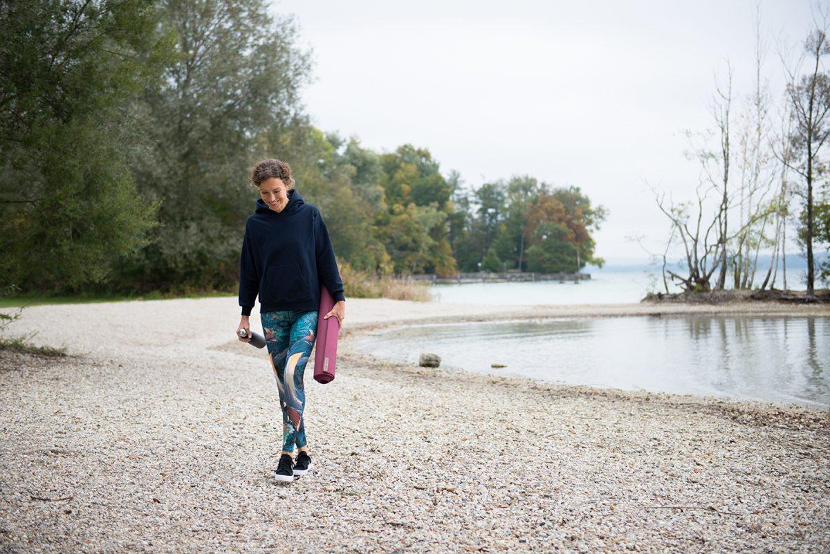 Yogafotografie von Yogalehrerin Ranja Weis am Ufer des Starnberger Sees mit Yogamatte und Trinkflasche in der Hand. |Felix Krammer Fotografie