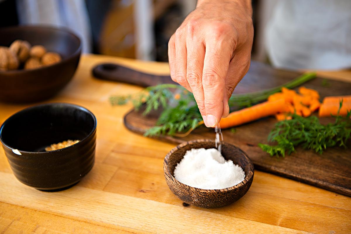 Salz rieselt in eine Schale. |Felix Krammer Fotografie