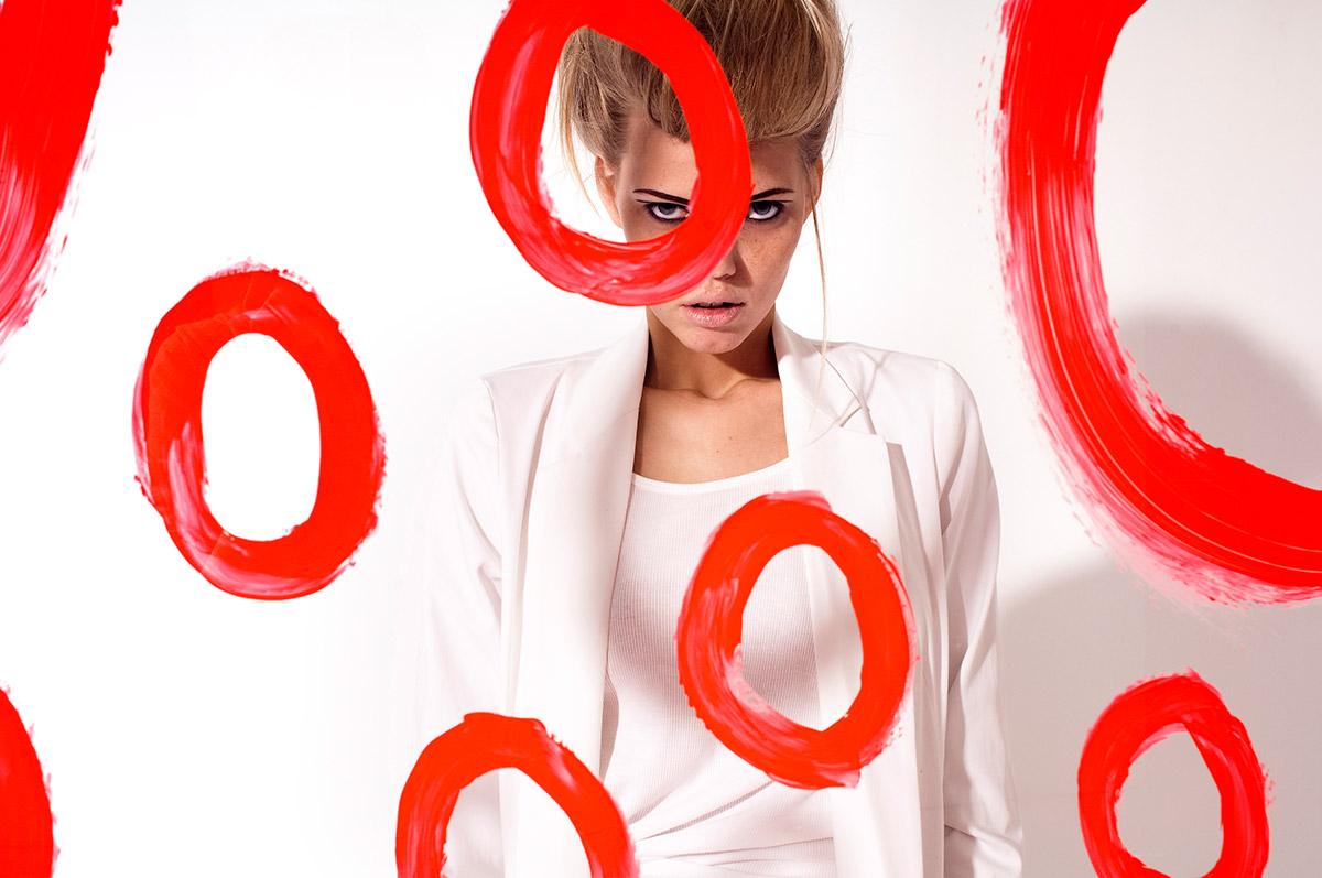 Fashion Fotografie eines Models hinter einer Glasscheibe auf die rote Kreise aufgemalt sind  Felix Krammer Fotografie