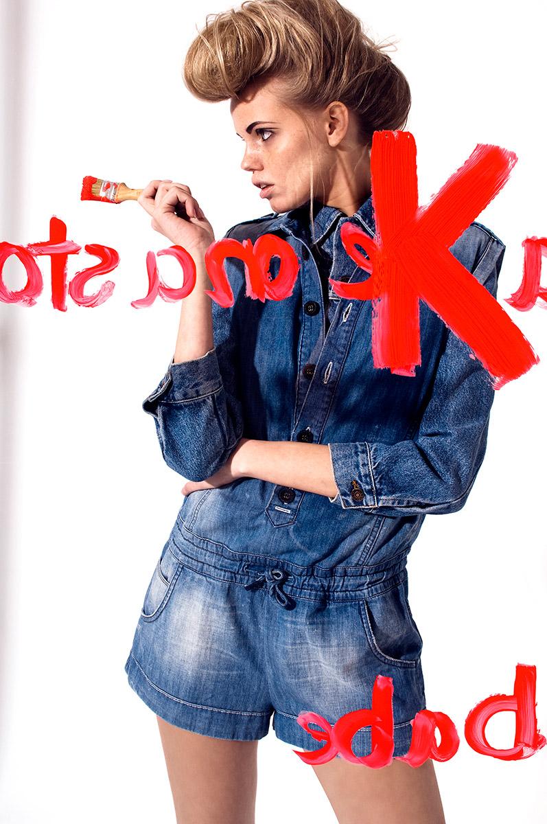 Fashion Fotografie eines Models hinter einer Glasscheibe mit rotem Pinsel in der Hand. |Felix Krammer Fotografie