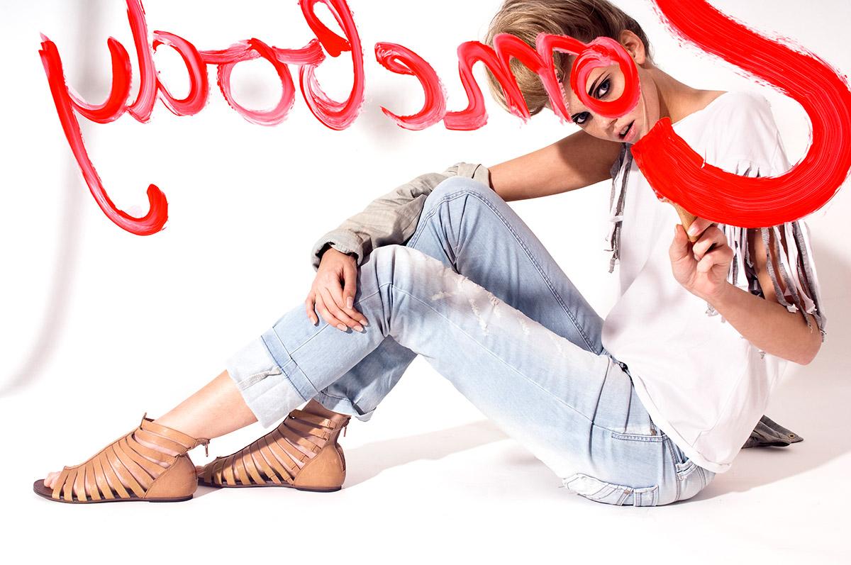 Fashion Fotografie eines Models hinter einer Glasscheibe malend mit Pinsel und roter Farbe.  Felix Krammer Fotografie