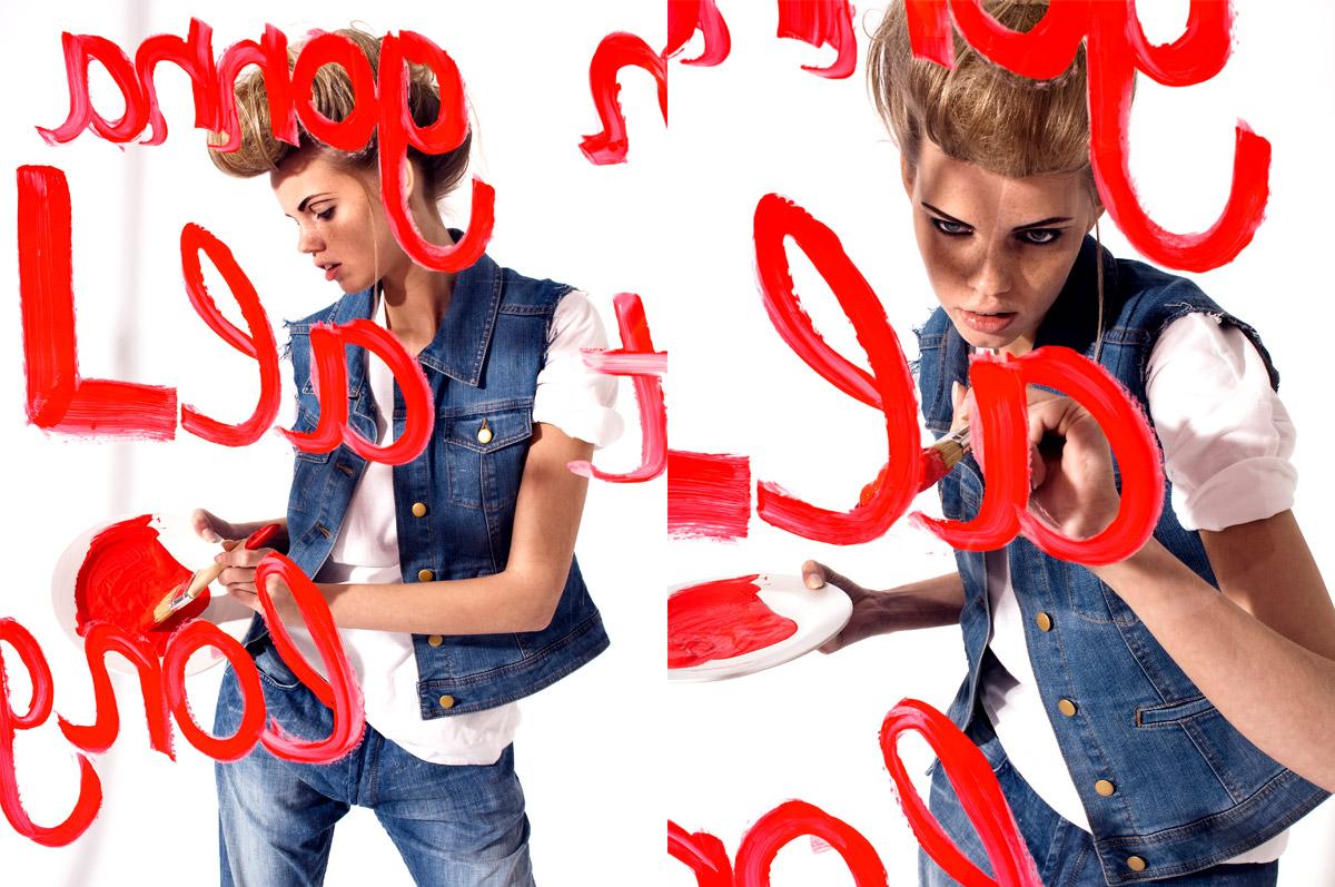 Modefotografie eines Models hinter einer Glasscheibe malend mit Pinsel und roter Farbe.  Felix Krammer Fotografie