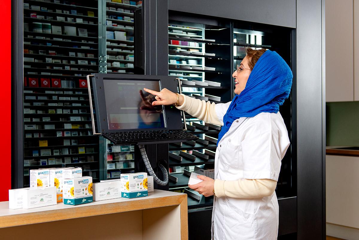 Unternehmensfotografie - Apothekerin tippt auf Display des computergesteuerten Warenlagers |Felix Krammer Fotografie