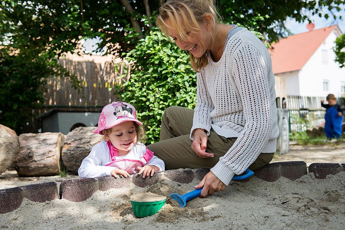 Kindergartenfotografie einer Erzieherin mit Kind beim Spielen im Sandkasten  Felix Krammer Fotografie