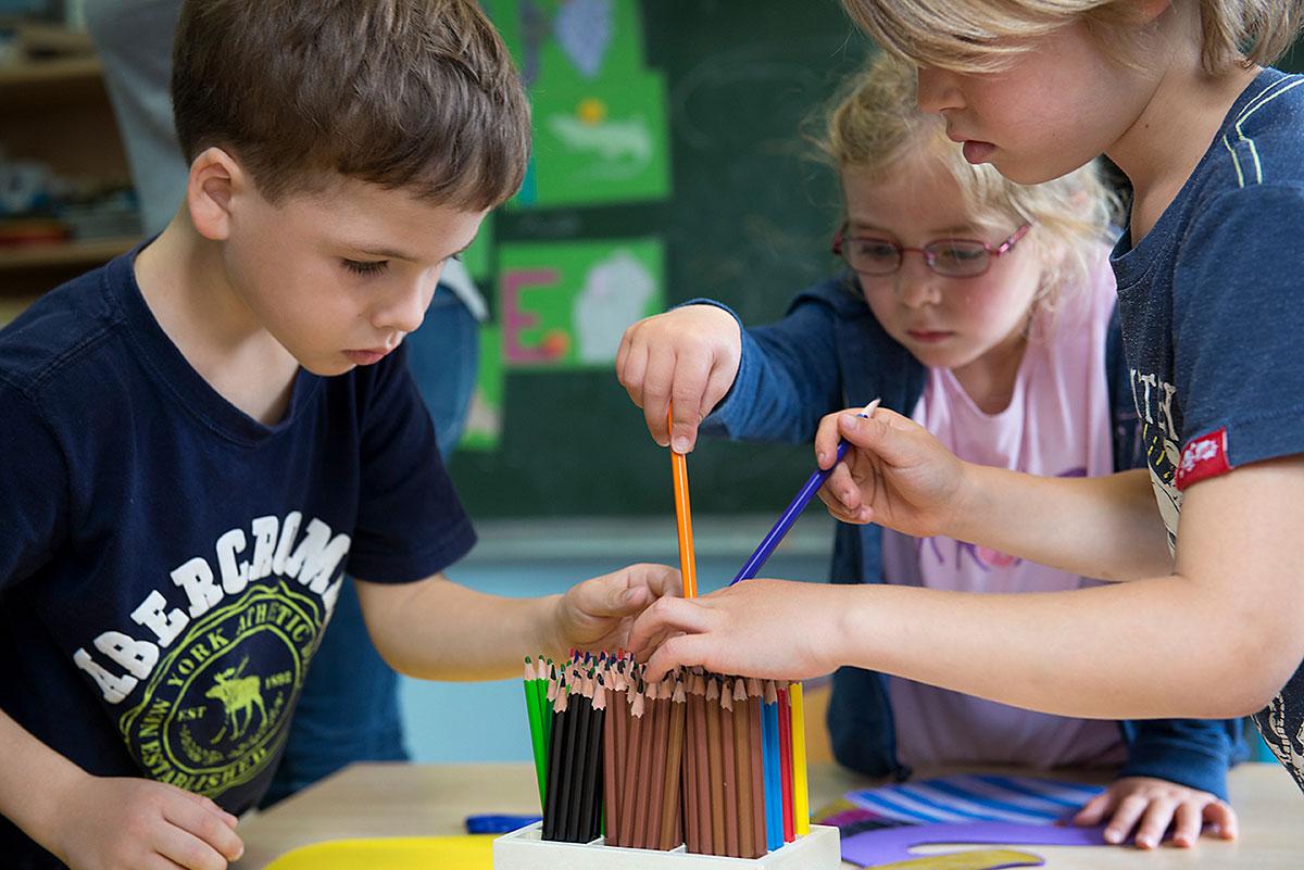 Kindergartenfotografie , 3 Kinder sortieren Holzmalstifte ein  Felix Krammer Fotografie