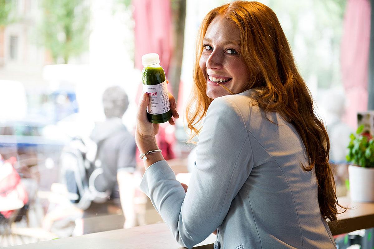 Junge Frau sitzt mit Smootie am Fenster - Werbefotografie für Dean & David |Felix Krammer Fotografie