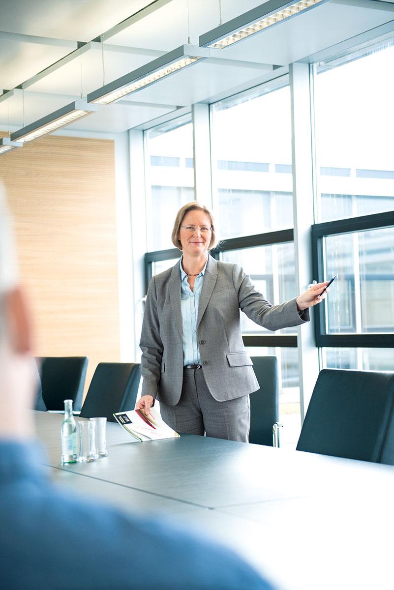 Werbefotografie mit Friederike Sturm, Präsidentin der staatlichen Lotterieverwaltung, in Konferenzraum stehend vor Fenster |Felix Krammer Fotografie
