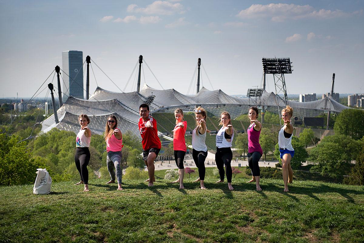 Yogafotografie für die Yoganacht München 2018. Yogis in der Krieger 2 Haltung vor dem Olympiastadion.  Felix Krammer Fotografie